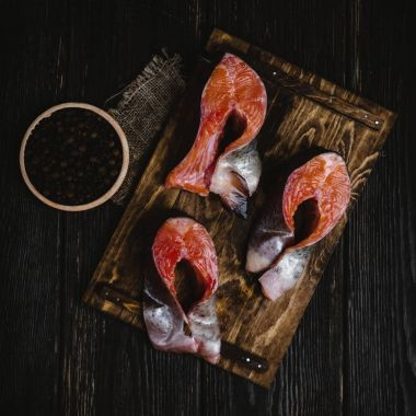 top view of sliced salmon fish on wooden cutting board with sackcloth and peppercorns on rustic table