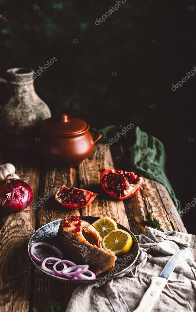 Baked salmon steak with lemon and onion on plate with pomegranate on wooden table
