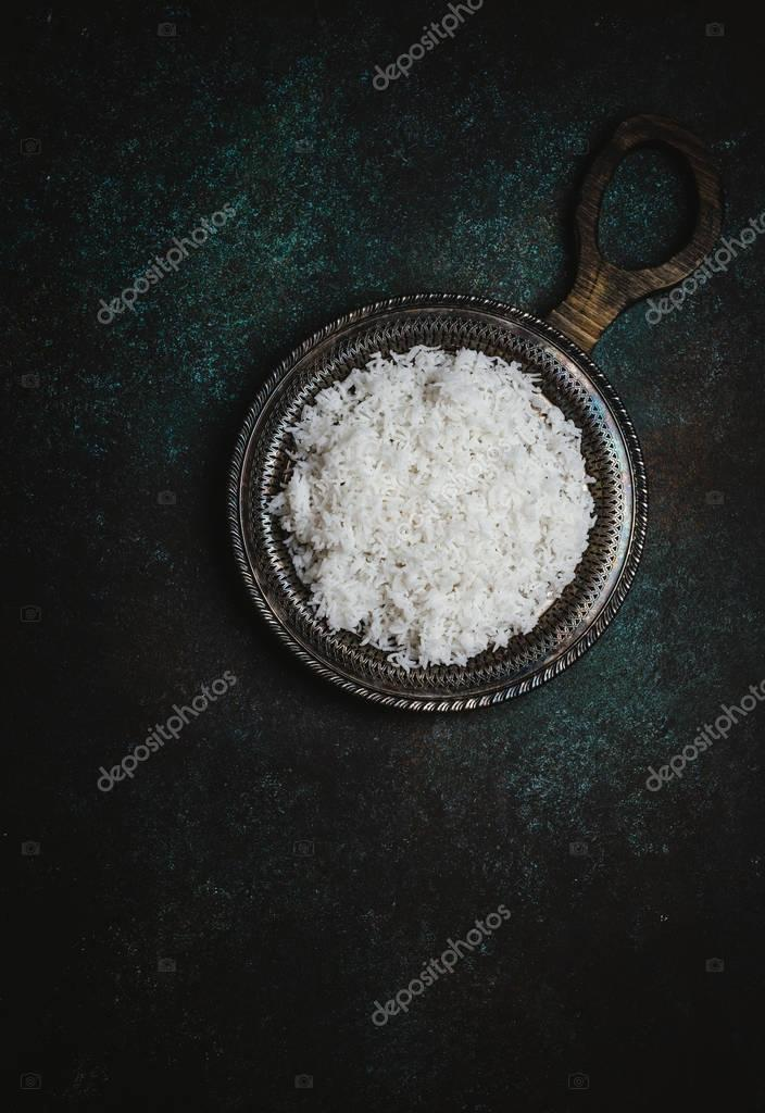 Top view of cooked white rice on rustic metal tray on dark table