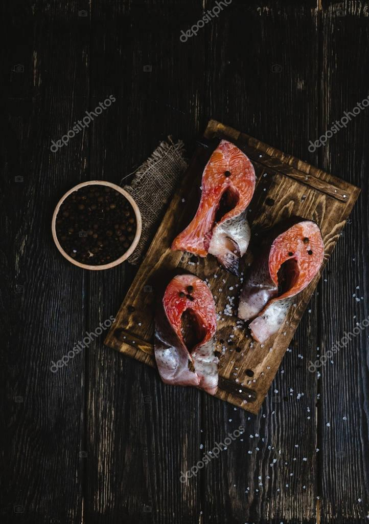 top view of sliced salmon fish on wooden cutting board with sackcloth, salt and peppercorns on rustic table