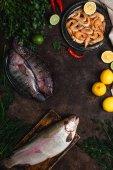 pohled shora ze syrové ryby, krevety, chilli papričky, byliny s citrony a ubrus na temné stolu