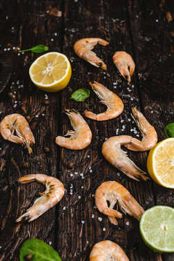 close-up view of delicious shrimp with citrus fruits and basil leaves on rustic wooden table