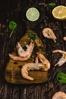 close-up view of delicious shrimp with citrus fruits on rustic wooden table