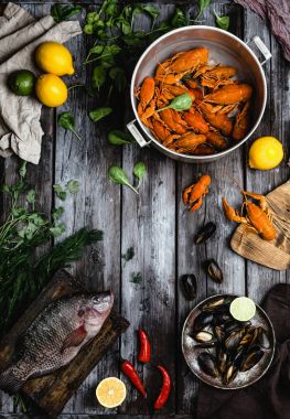 top view of various delicious seafood with lemons and herbs on rustic wooden table
