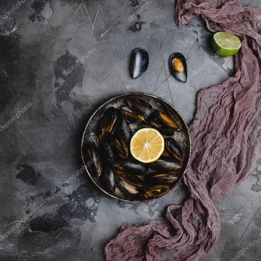 top view of delicious mussels with shells on vintage plate and lime with lemon and cloth on grey