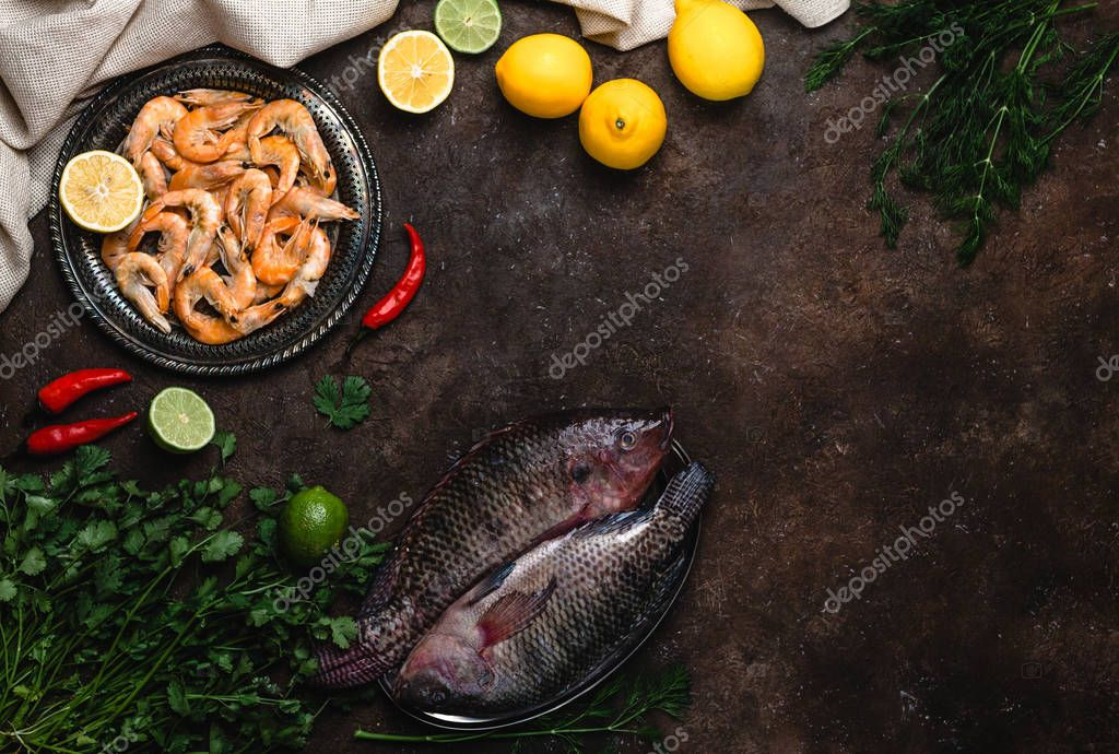 raw fish, chili peppers, shrimp, herbs with lemons and tablecloth on dark table top