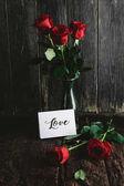Fotografia Rose rosse in vaso e cartolina dauguri di amore su fondo di legno misero, concetto di giorno di San Valentino