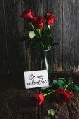 Fotografia Rose rosse in vaso e sia la mia cartolina di San Valentino su fondo di legno misero