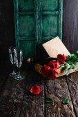 Fotografia Rose rosse e bottiglia di champagne, bicchieri e busta sul vassoio, concetto di giorno di San Valentino