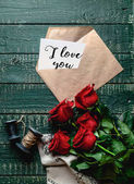 Fotografia vista superiore di red rose e busta con io ti amo cartolina di San Valentino su fondo di legno