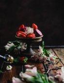 mísa s macarons a jahody na dřevěný stůl s květinami a láhev šampaňského a nůžky