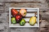 pohled z jablek a hrušek v dřevěné krabici na rustikální stůl