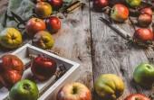 Detailní pohled jablka, hrušky, dřevěná krabice, nůž, nůžky, ruční váhy a utěrku na rustikální stolní