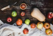 Fotografie top view of pumpkin, apples, blood oranges, kitchen towel and knife on wooden table