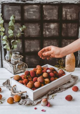 cropped image of female hand and pile of lychees in wooden box on table