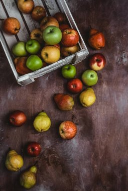 top view of box with apples and pears on wooden surface