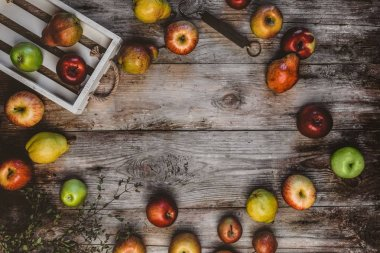 top view of wooden box, hand scales, apples and pears on rustic table