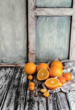 Kitchen towel, oranges, tangerines and kumquats on wooden table stock vector