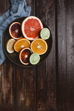 top view of halfs of orange, grapefruit, lime, blood orange and lemon in plate and kitchen towel on wooden table