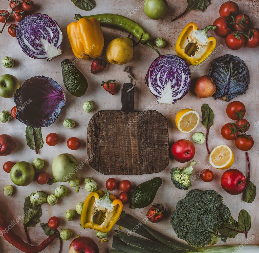 Top view of wooden cutting board surrounded by different fruits and vegetables on table