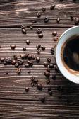 Fotografie šálek černé kávy a kávových zrn na tmavém pozadí