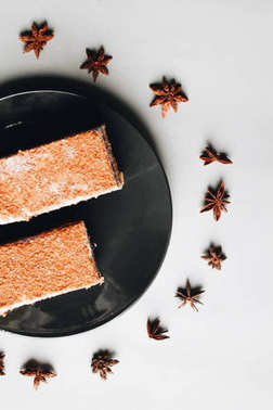 two pieces of delicious cake on black plate, anise stars around plate