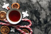 Fotografie candy canes, slices of dry oranges  and cup of tea on dark stone table