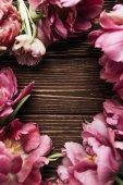 Fotografie Kulatý rám krásné jarní Růžové květiny na dřevěné pozadí