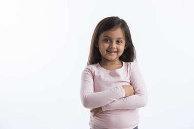 Portrait of an adorable little girl smiling standing with her arms crossed