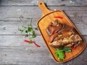 Fotografie Geschmortes Schweinefleisch mit Chili Paprika auf Schneidbrett aus Holz
