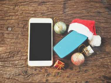 top view of audio speaker with smartphone and christmas hat on wooden table