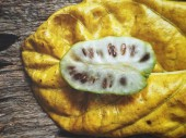 Green Noni fruits with leaf on wooden background