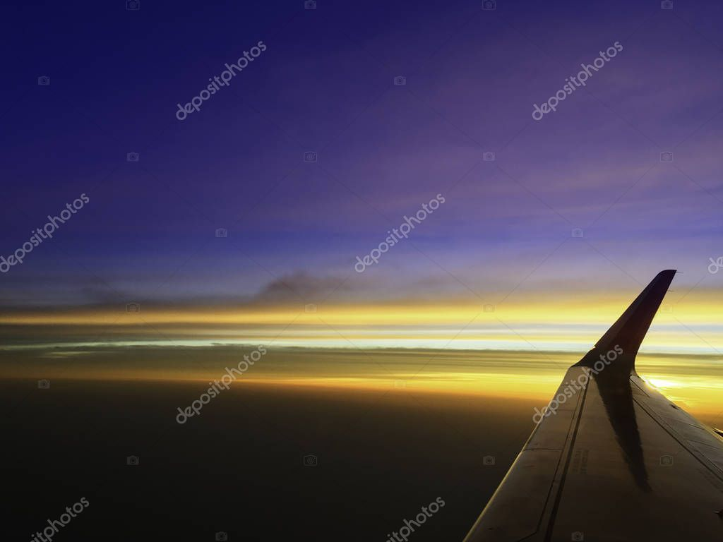 beautiful twilight cloud sky through airplane wing
