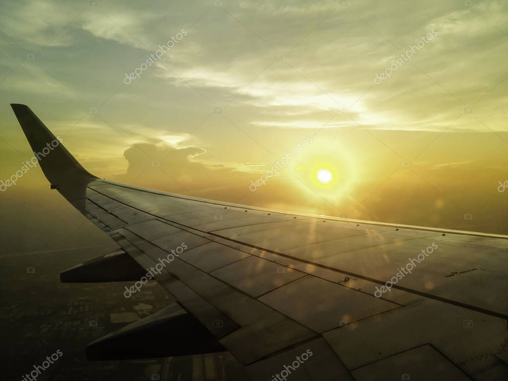 airplane wing in the sky with sun setting in background