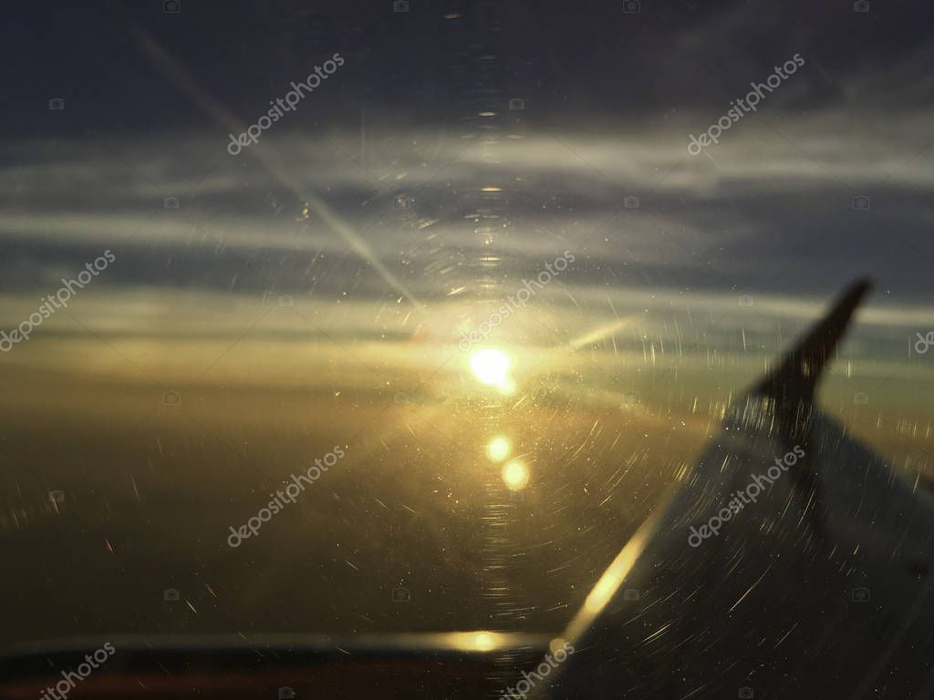 airplane window focus with sun set on horizon cloud sky through