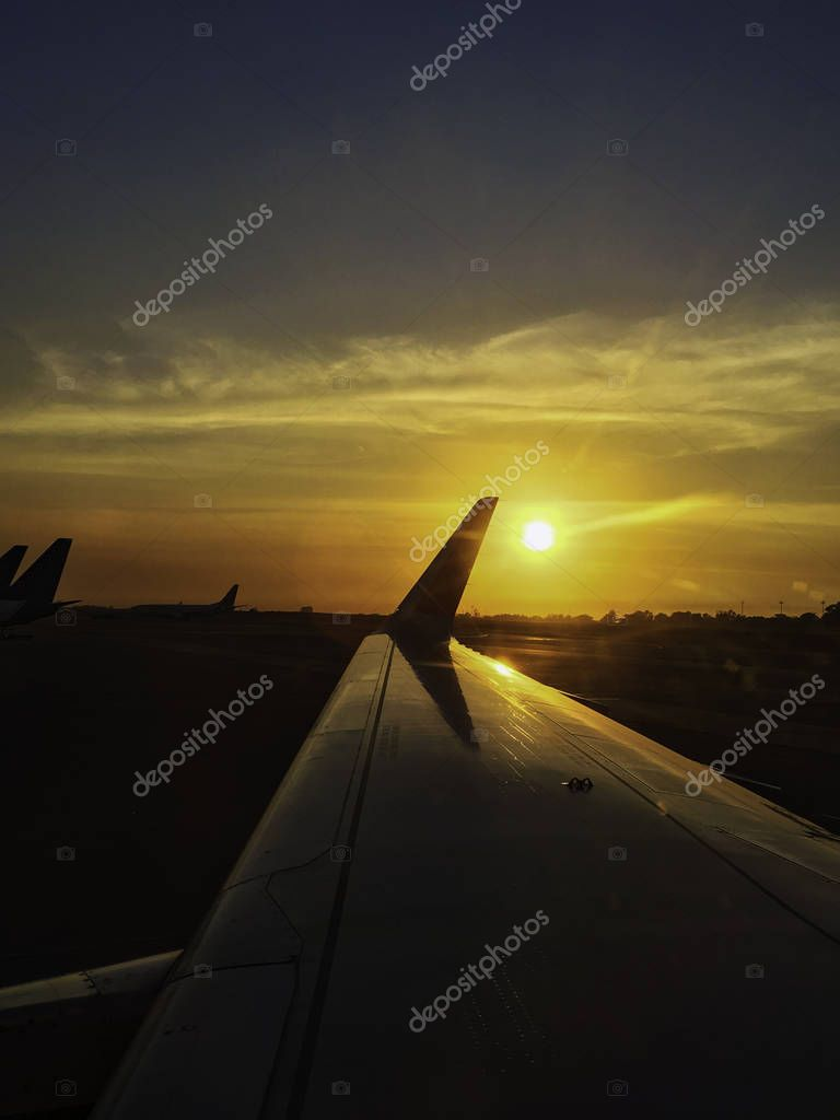 sun set at the horizon along the plane wing