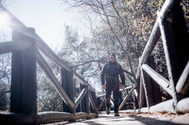 Mountaineer man walking on a bridge