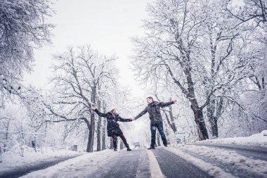 Couple man and woman enjoy great snowfall.