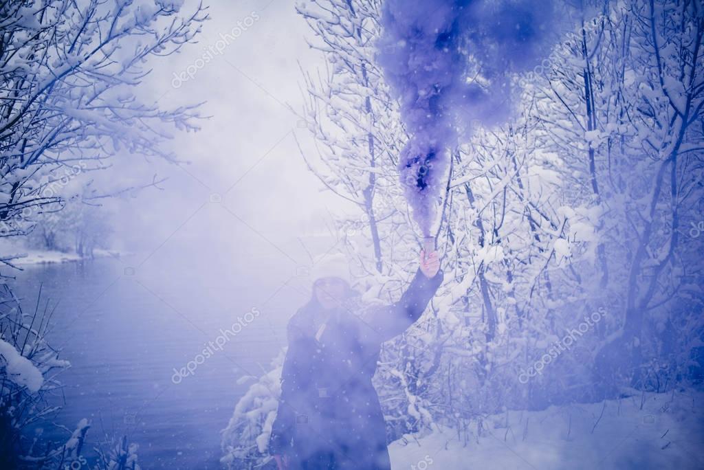 Girl in snow blue smoke bomb.