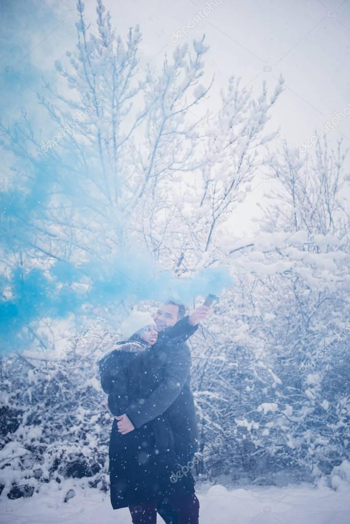 Girl and man in snow blue smoke bomb.