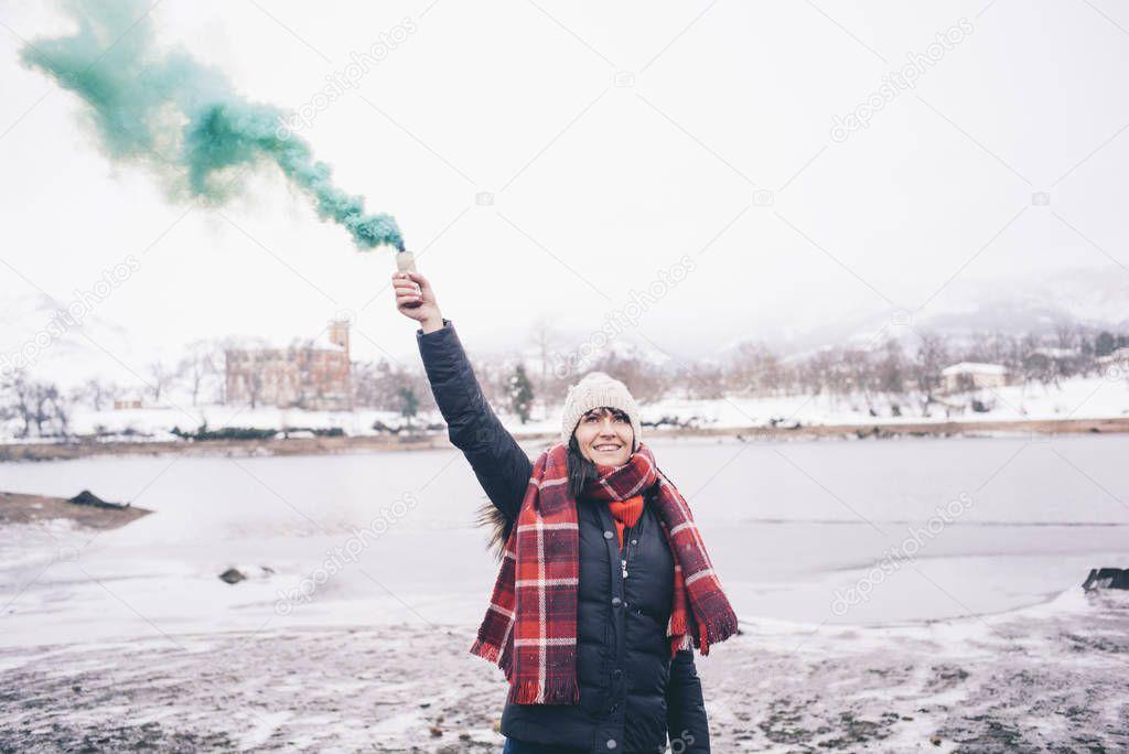 Woman on lake with smoke bomb.