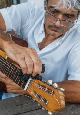 Attractive white hair man cleaning a guitar.