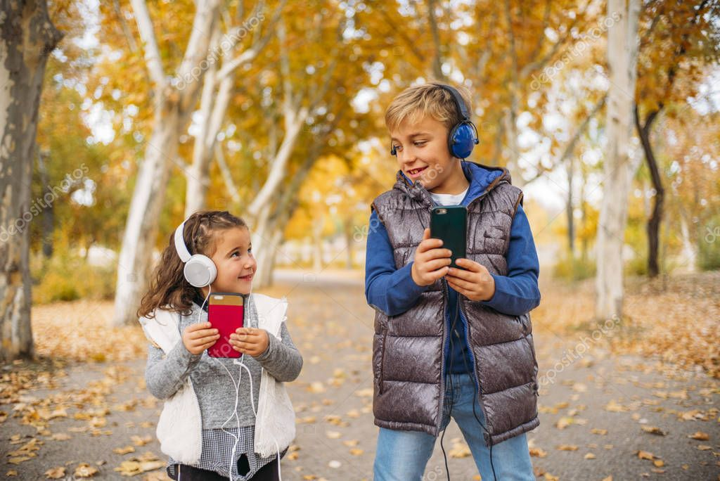 Children listen to music in autumn landscape