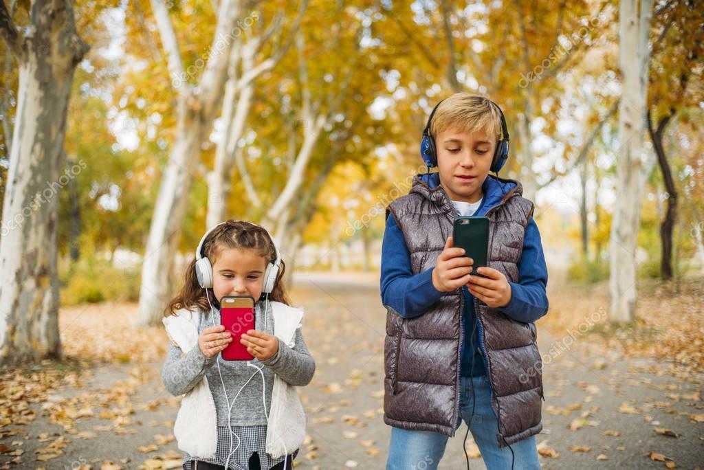 Children listen to music in autumn landscape