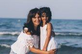 Fotografie Mutter und Tochter stellen Blick in die Kamera am Strand bei Sonnenuntergang