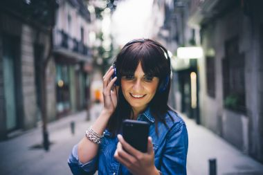 Pretty woman listening to music with headphones.