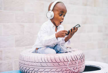 The small African boy listens to music with headphones sitting on tires.