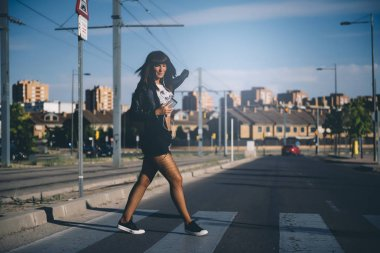 Young woman listening to music with phone on pedestrian crossing.