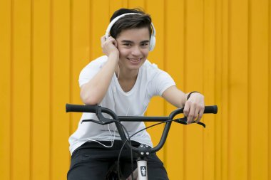 Young boy listens to music with headphones on a bicycle.