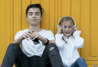 Boy and little girl listen to music with headphones.